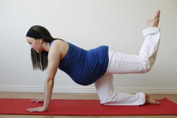 Беременная выполняют стойку на коленях и ладонях