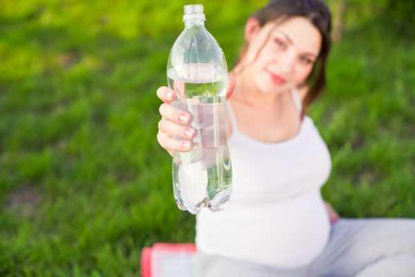 Беременная женщина держит бутылку с водой