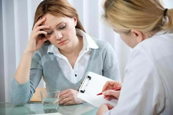 женщина, поддерживая голову, сидит перед врачом