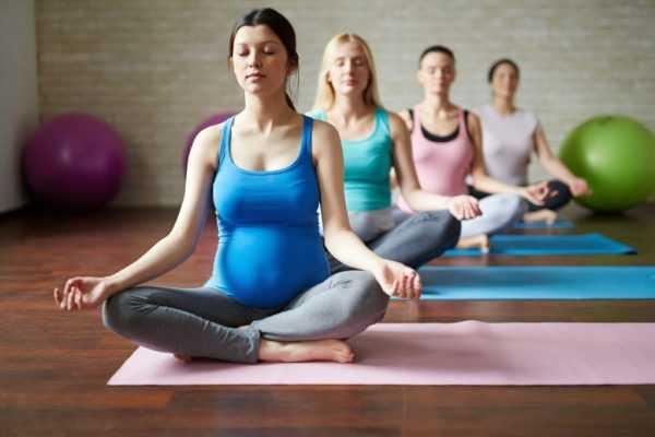 В спортивном зале в позе лотоса сидят четыре беременные женщины