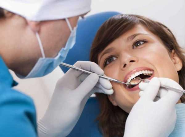 стоматолог проверяет зубы у женщины