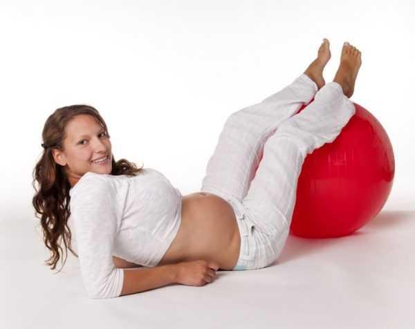 Беременная лежит на полу, опираясь на локти и положив ноги на гимнастический мяч