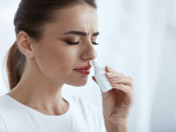 женщина вводит в нос флакон с назальным средством