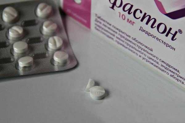 Целая таблетка Дюфастона и половинка, рядом упаковка и блистер с таблетками