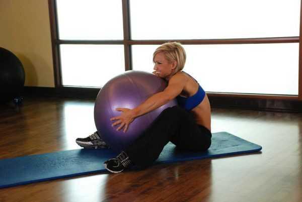 Женщина с фитболом между ног