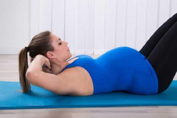 Беременная выполняет упражнение на пресс