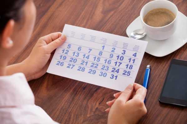 Женщина сидит за столом и смотрит на календарь