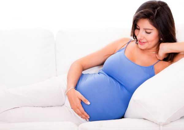 Беременная женщина улыбается и гладит свой живот