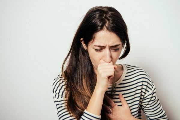 девушка закрыла рот кулаком, другой рукой держась за грудь