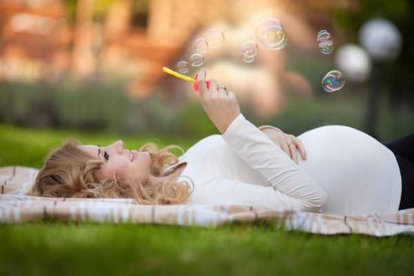 Беременная женщина лежит и пускает мыльные пузыри
