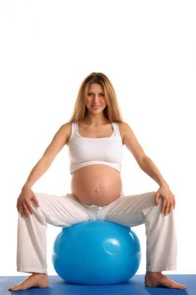 Беременная женщина сидит на фитболе