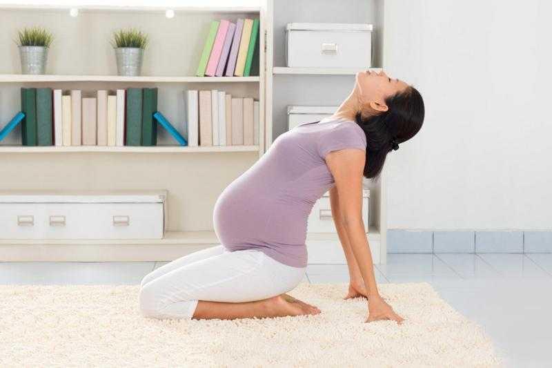 Беременная занимается йогой