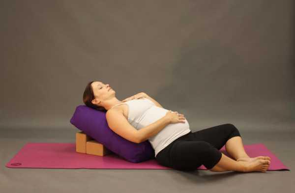 Беременная выполняет позу йоги, лёжа на болстере