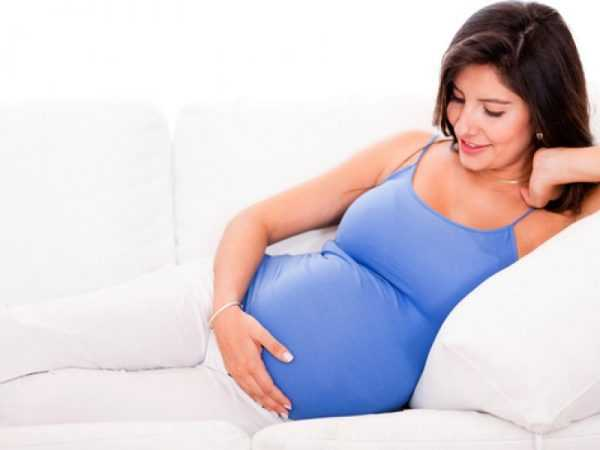 немолодая беременная полулежит на диване