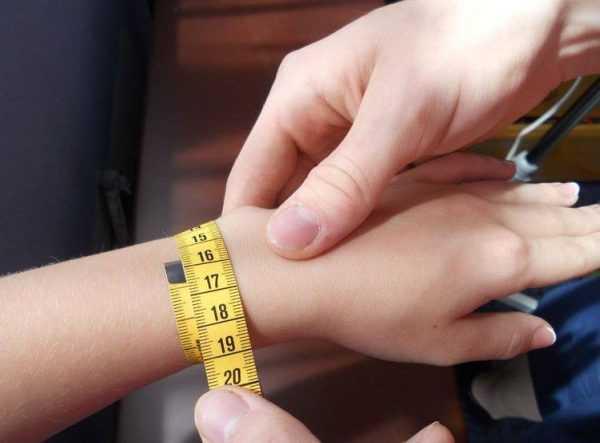Женщине измеряют окружность запястья