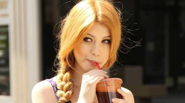 девушка пьёт коричневую жидкость через соломинку