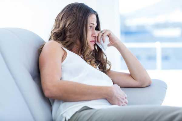 беременная сидит с грустным выражением лица, держа у глаз платок