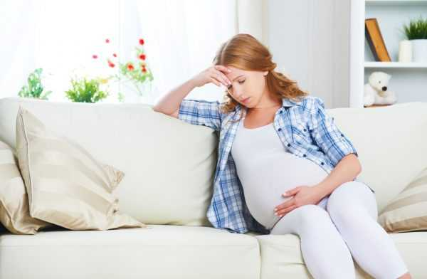 беременная сидит на диване, держась за голову