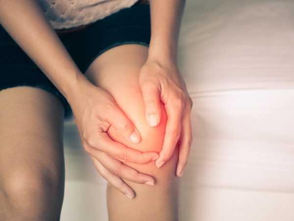 девушка держится за покрасневший коленный сустав