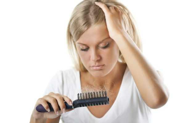 девушка грустно смотрит на расчёску с клоками волос