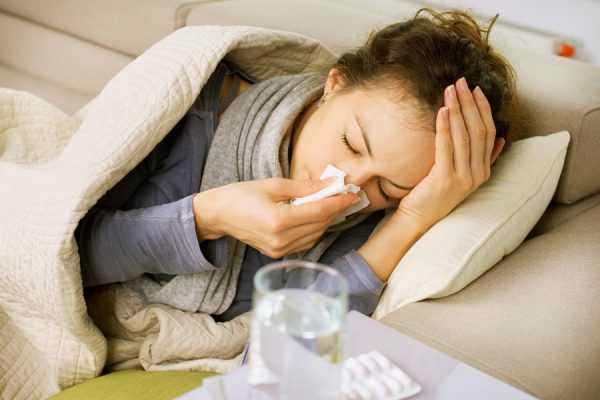 женщина лежит под одеялом, с салфеткой у носа
