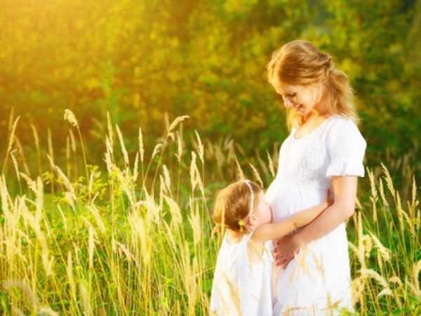 беременная на лесной поляне с дочкой