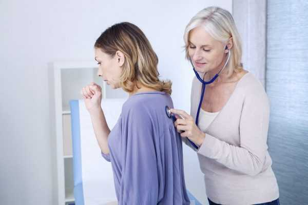 врач прослушивает лёгкие девушки, которая кашляет