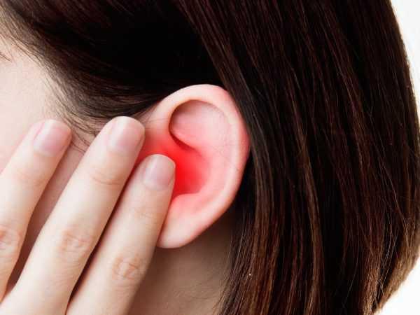 Девушка держится за воспалённое ухо