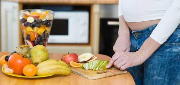 Беременная режет фрукты