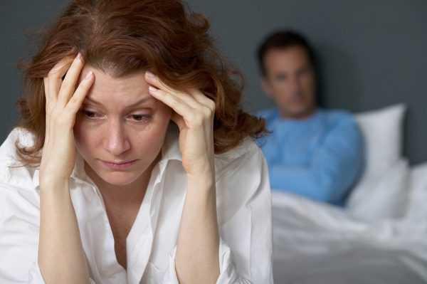Расстроенная женщина держится руками за голову