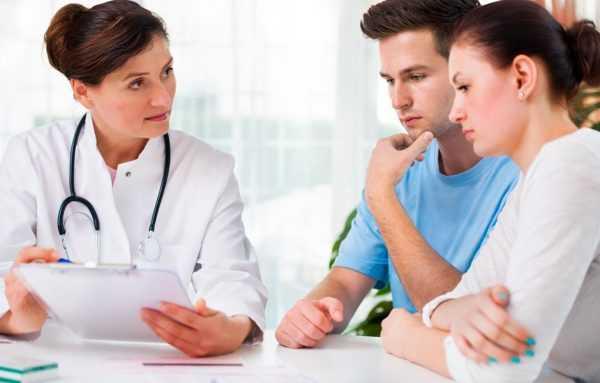 молодая пара смотрит на листок в руках врача
