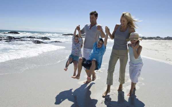 родители и трое детей на берегу моря