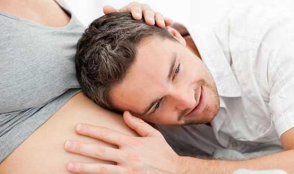 голова и рука мужчины лежит на животе у беременной