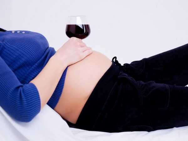 беременная держит бокал вина на животе