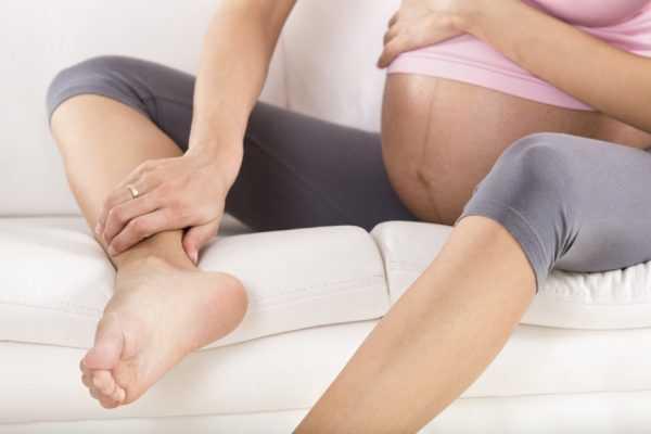 Беременная женщина сидит на диване и держится за ногу