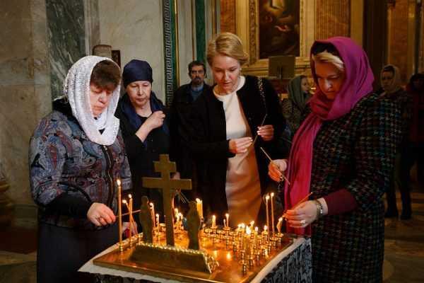 Женщины ставят свечи за упокой