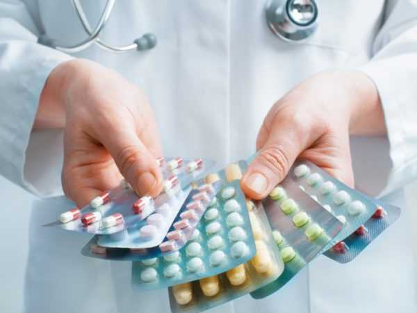Врач держит таблетки в руках