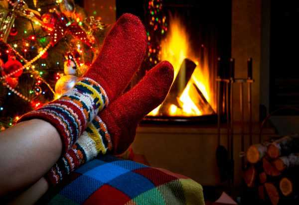 Тёплые носки на женских ногах, рядом — горящий камин