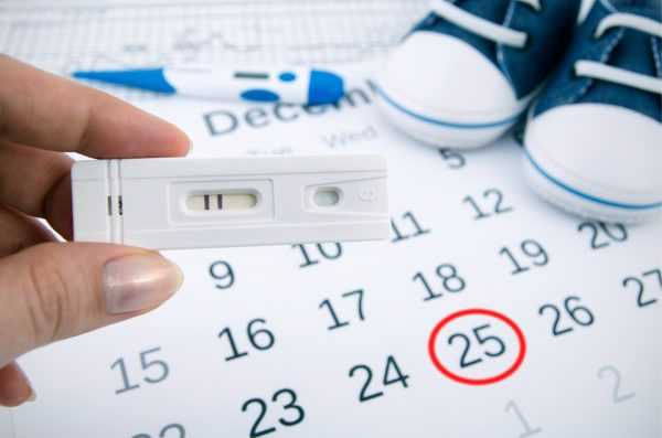 Тест на беременность, календарь и детские пинетки