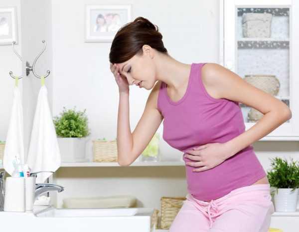 беременная женщина сидит у раковины