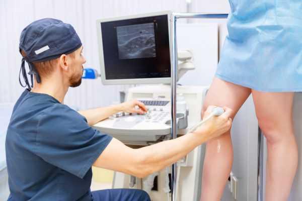 врач проводит пациентке ультразвуковое исследование вен нижних конечностей