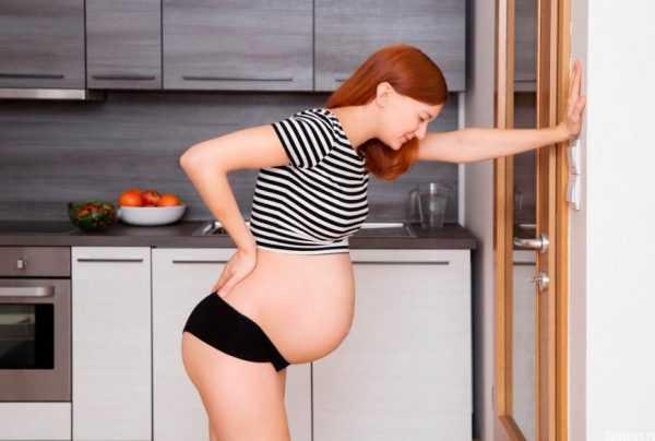 беременная держится за поясницу
