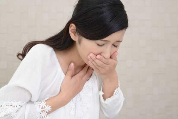 Женщина зажимает рукой рот при тошноте