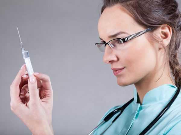 Женщина-медик со шприцем в руке