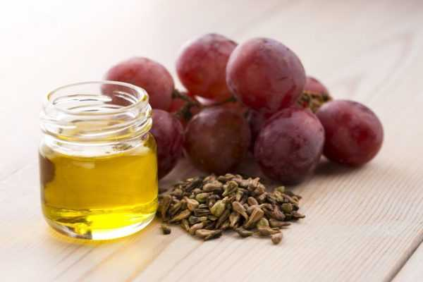 виноградные косточки с красными ягодами и банкой масла
