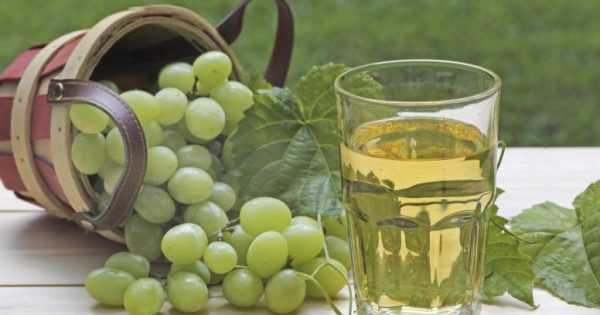 стакан виноградного сока и свежий виноград на столе
