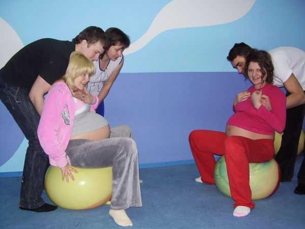 Занятие для будущих родителей по подготовке к родам: беременные сидят на фитболе, а мужья поддерживают их сзади