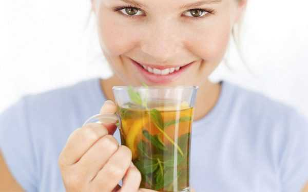 женщина держит к руках стакан зеленого чая с лимоном