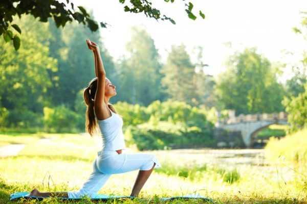 Женщина делает зарядку на свежем воздухе