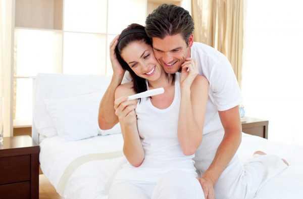 Женщина и мужчина смотрят с улыбкой на тест на беременность, сидя на белой постели